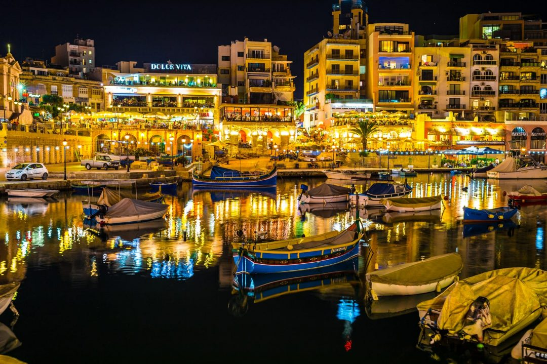 Lots of traditional Maltese boats in the sea at night with a view of St. Julian's in the background