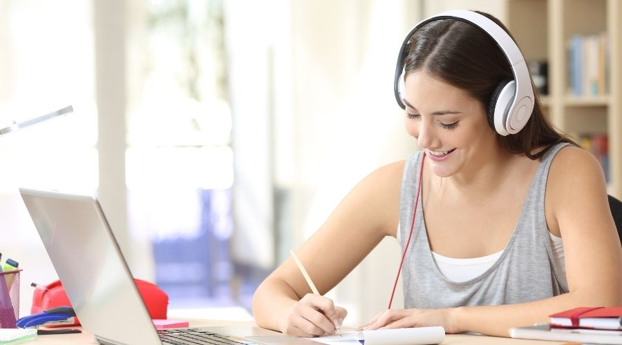 female student wearing headphones working laptop