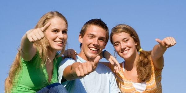 three teenagers smiling with thumbs up