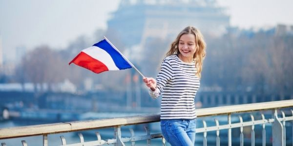 A French female young adult waving a French flag