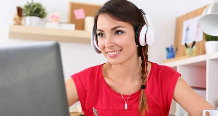 female student with laptop and headset having one-to-one English tuition online
