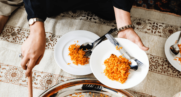 woman serving Arabic food on plate